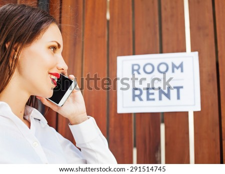 """woman calling the house owner in front of """"Room for rent"""" sign - stock photo"""