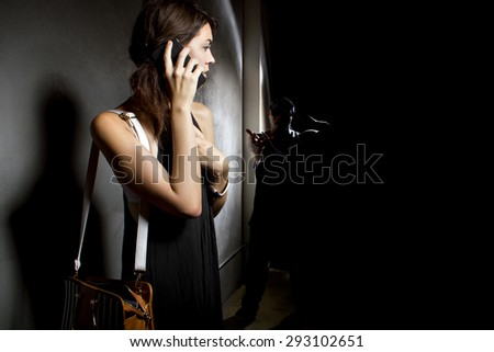 Woman calling 911 with a cell phone while alone in a dark street alley.  A criminal is stalking her from the shadows.  She is calling for help. - stock photo