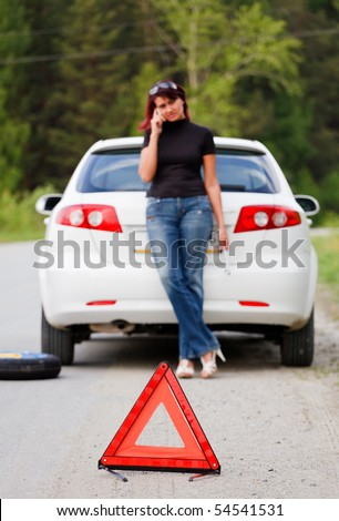 Woman calls to a service standing by a white car. Focus is on the red triangle sign