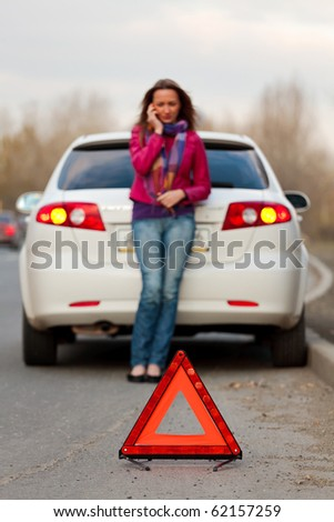 Woman calls to a service standing by a white car. Focus is on the red triangle sign. Evening light. - stock photo