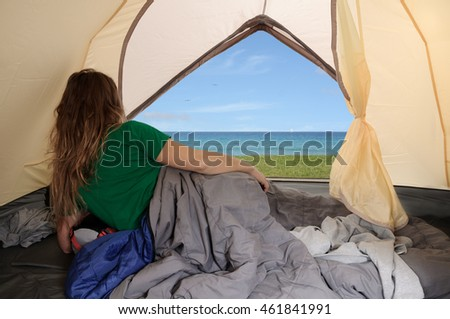 Woman camping in tent at tranquil campsite