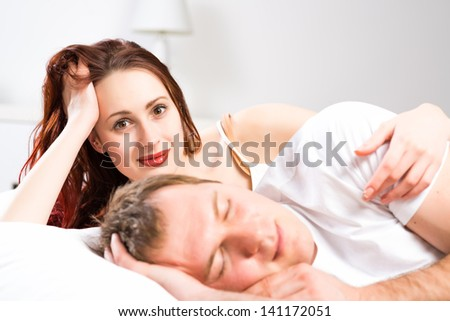 woman can not sleep with her husband in bed - stock photo