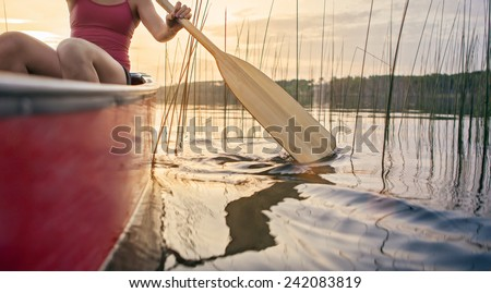 Woman canoeing at sunset on Jackfish Lake, Manitoba. - stock photo