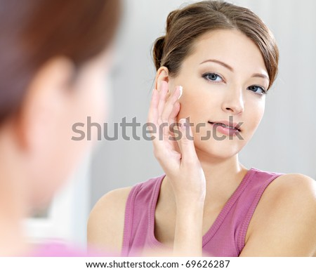 Woman caring of her  beautiful skin on the  face standing near mirror in the bathroom - stock photo