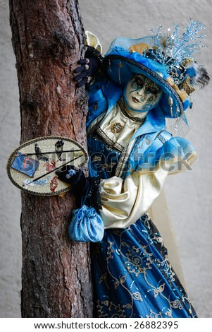 Woman carnival mask dressed in blue and yellow against a tree (Annecy/France) - stock photo