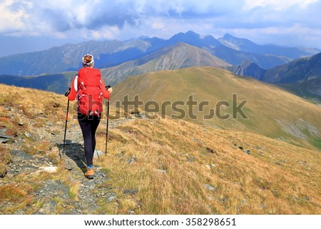 Woman carries a backpack on a trail across the mountain - stock photo