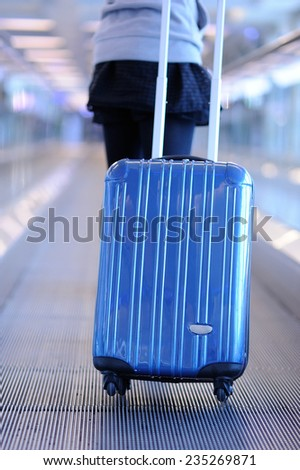 Woman carries luggage at the airport - stock photo