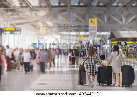 woman carries luggage at the airport terminal. - stock photo