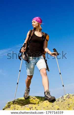 Woman carrying a backpack climbs rocky mountains  - stock photo