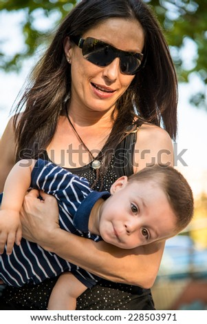 woman carrying a child in her arms - stock photo