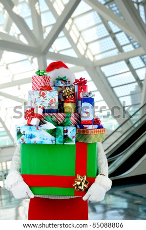 Woman carrying a large stack of christmas presents in a modern shopping mall. Woman is hidden behind the presents.