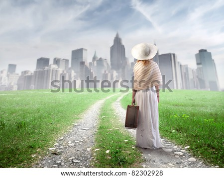 Woman carrying a suitcase and approaching a big city - stock photo