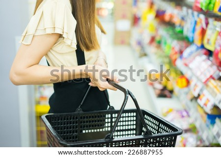 Woman carrying basket while shopping in the supermarket - stock photo