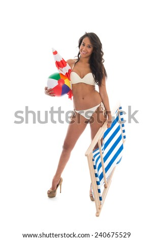 woman carrying beach chair and other attributes during vacation - stock photo