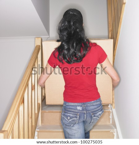 Woman carrying box up stairs in new house - stock photo