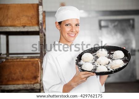 Woman Carrying Dough Balls In Baking Tray - stock photo