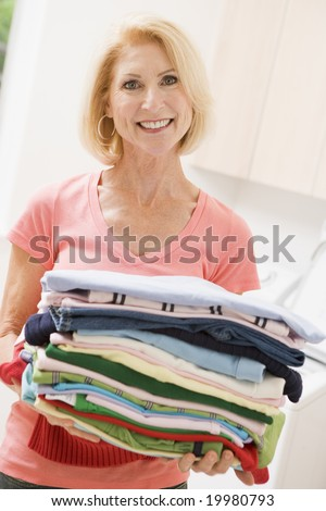 Woman Carrying Folded Up Laundry - stock photo