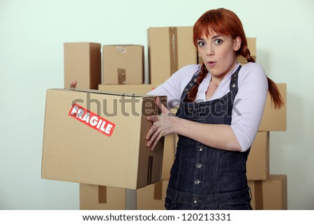 Woman carrying fragile box - stock photo