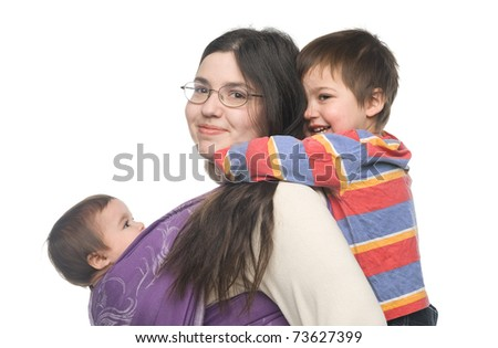 Woman carrying her little daughter in a sling. Her son hugging her from behind - stock photo