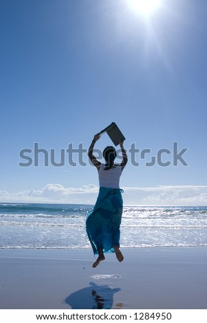Woman carrying laptop computer jumping around at the beach - stock photo