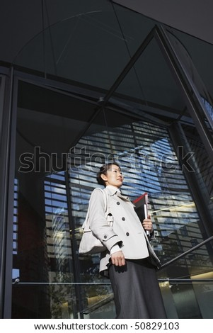 Woman Carrying Notebooks, standing outside, low angle view