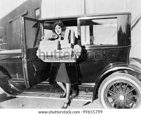 Woman carrying packages from car - stock photo
