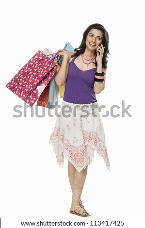 Woman carrying shopping bags and talking on mobile phone - stock photo
