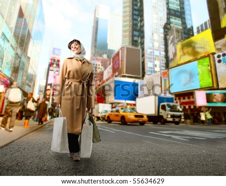 Woman carrying some shopping bags walking on a city street - stock photo