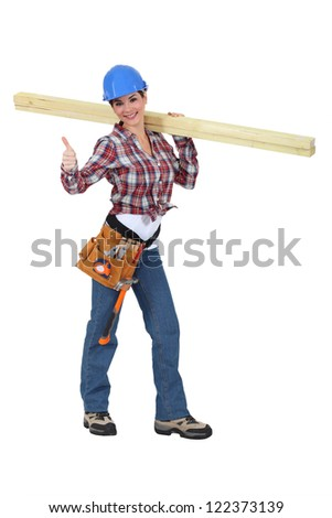 Woman carrying two planks of wood - stock photo