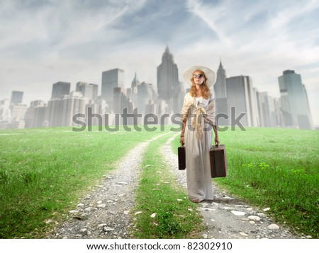 Woman carrying two suitcases and coming from a big city - stock photo