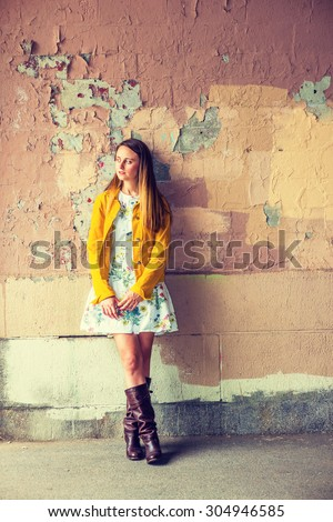 Woman Casual Fashion. A pretty girl wearing flower patterned underdress, yellow corduroy jacket, brown leather high riding boots, standing by wall peeling off paints, looking away. Instagram effect. - stock photo