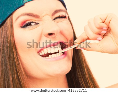 Woman casual style smiling teen girl holding a stick of chewing gum on toned photo. Youth style
