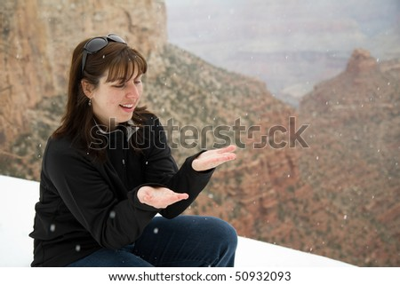Woman Catching Falling Snow - stock photo
