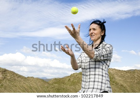 woman catching tennis ball in sand dunes