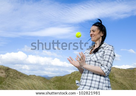 woman catching tennis ball in sand dunes with blue sky