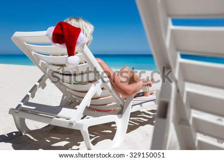 Woman celebrate christmas at caribbean sandy beach with turquoise sea water and white sand