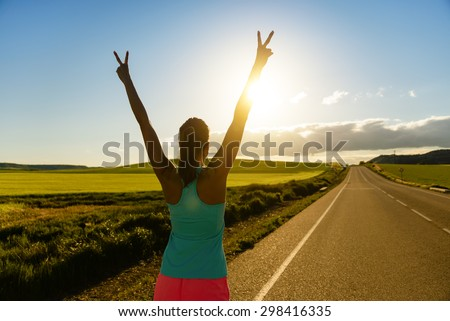 Woman celebrating running and training success on countryside road during sunset or sunrise. Female runner raising arms towards the sun. - stock photo