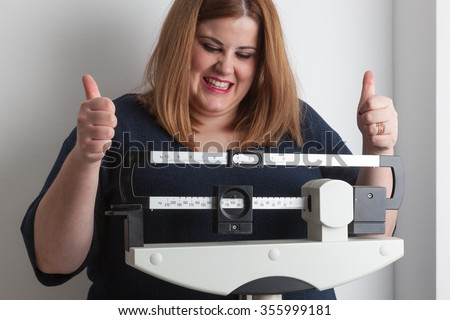 Woman celebrating weight loss on a medical weight scale - stock photo