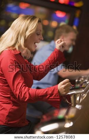 Woman celebrating win on slot machine at casino - stock photo