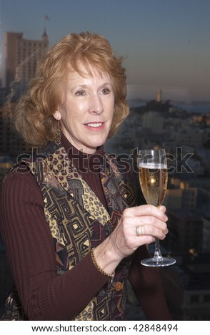 Woman celebrating with champagne in San Francisco Hotel with Coit tower in the background - stock photo