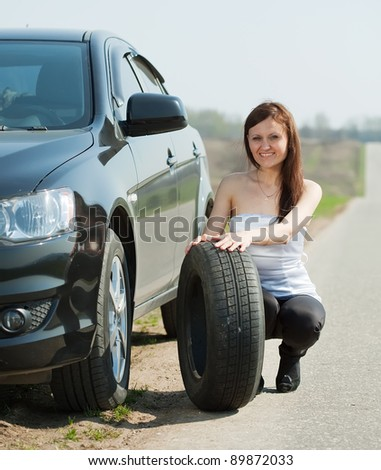 Woman changing car wheel at road - stock photo
