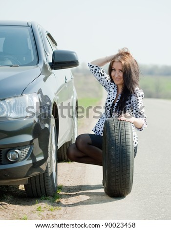 Woman changing car wheel at road - stock photo