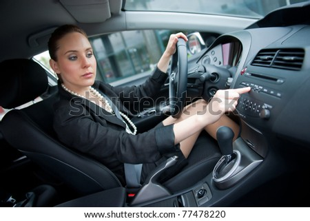 woman changing radio station while driving car