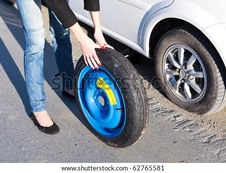 Woman changing the wheel