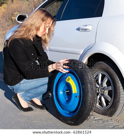Woman changing the wheel - stock photo