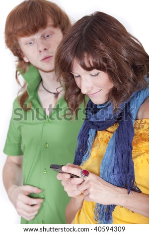 woman chatting with mobile phone - surprised man looking over shoulder - stock photo