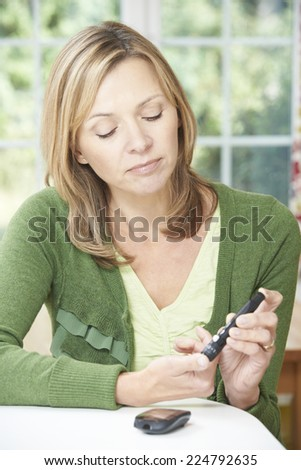 Woman Checking Blood Sugar Level At Home - stock photo