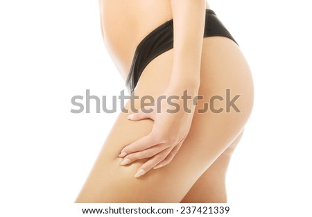 Woman checking fat on her thigh. - stock photo