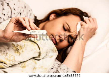 woman checking fever with digital thermomether girl with flu - stock photo