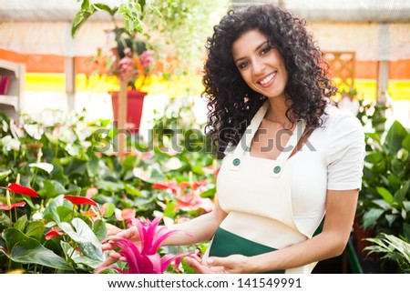 Woman checking flowers in a greenhouse - stock photo